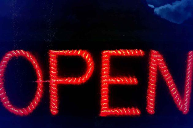 Foto Open Schild Neon LED Pop Art leuchtend auf schwarzem Hintergrund