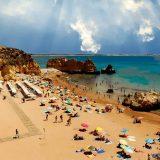 Foto Portugal Felsen Algarve Dona Ana Strand im Hintergrund Meia Preia Strand, Farben blau, türkis und braun, Himmel, Meerwasser,Sand, Kumulus Wolken