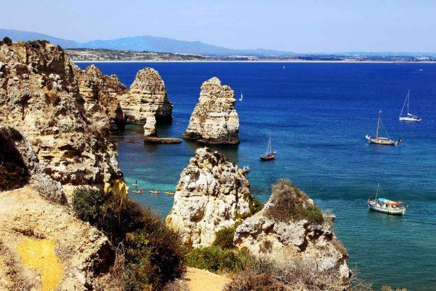 Foto Portugal Felsen Algarve mit Booten Hintergrund Strand Meia Preia, Farben blau, türkis und braun