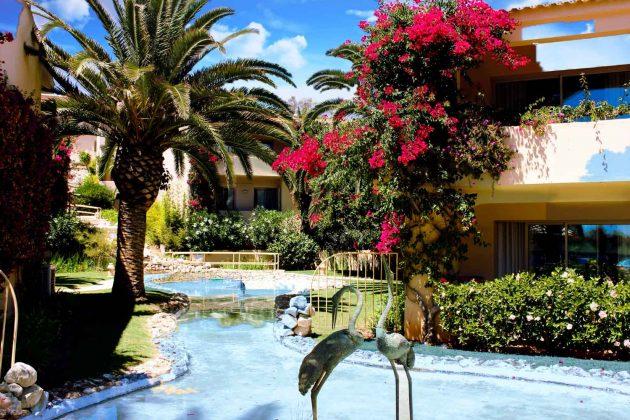 Foto Portugal Flamingos Skulptur an Teichanlage mit Palmen und Buganvilla, Farben blau, grün und lila, Himmel, Kumulus Wolken