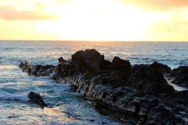 Foto Lavafelsen im Meer auf Lanzarote mit Kumuluswolken im Sonnenuntergang blau orange schwarz