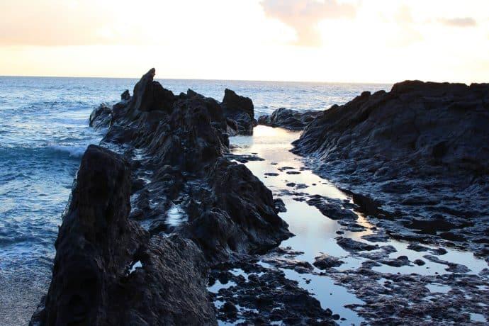 Foto Lavafelsen im Meer auf Lanzarote mit Kumuluswolken blau schwarz